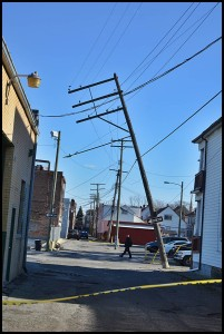 A utility pole leans toward falling over behind Mostek and Paint Company.