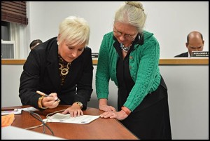 Over two years ago City Manager Katrina Powell (left) started off her job here by signing her employment contract with Mayor Karen Majewski. Now it appears a bare majority of councilmembers are against extending her contract, which expires on June 30.