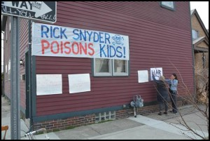 A large banner criticizing Gov. Rick Snyder for the way he handled the Flint water crisis greeted him during his visit with community leaders at the Polka Dot Café at Brombach and Yemans.